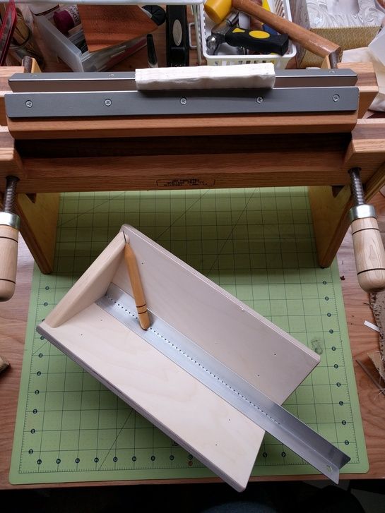 Image of a blank book block in a finishing press with backing boards, behind a punching cradle with awl and punching guide