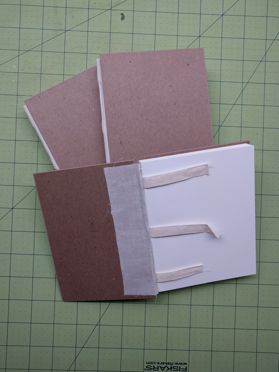 Image of three blank book blocks with boards attached, two closed and one open to reveal attached mull and loose tapes