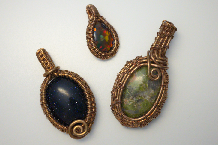 Three cabochon pendants wrapped with copper wire